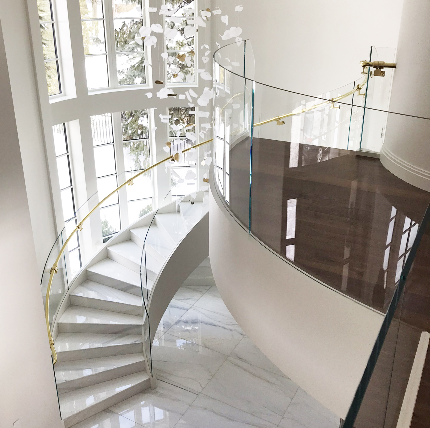 curved stairway with glass panel railing